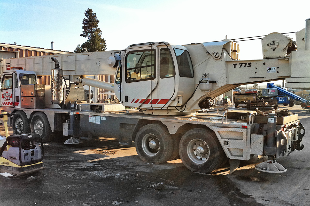 White utility truck containing a crane