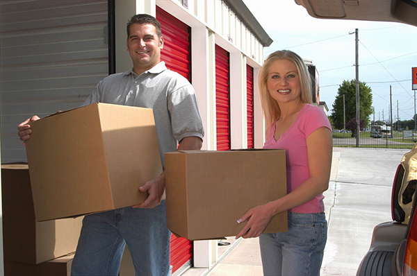 A man and woman each carrying a box outside