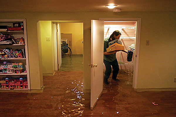 Man carrying items in a basement full of water due to a flood