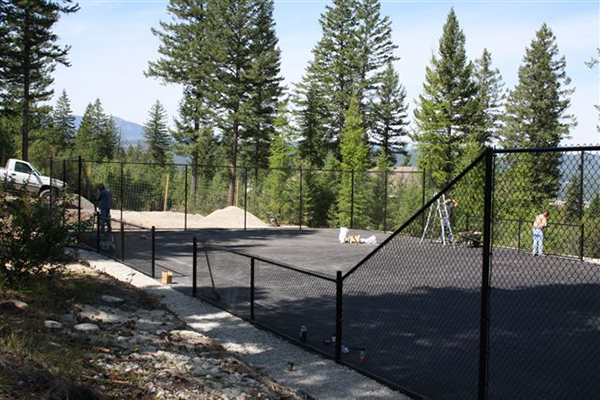 Metal fencing around an area paved with asphalt