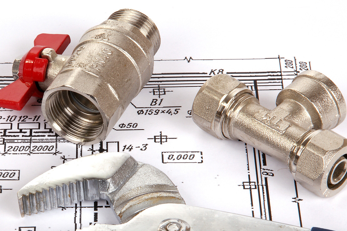 brass coloured plumbing components next to a wrench on a blueprint outlining pipework
