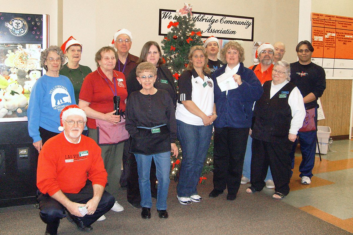 Large group of people posing for a staff picture surrounding a Christmas tree