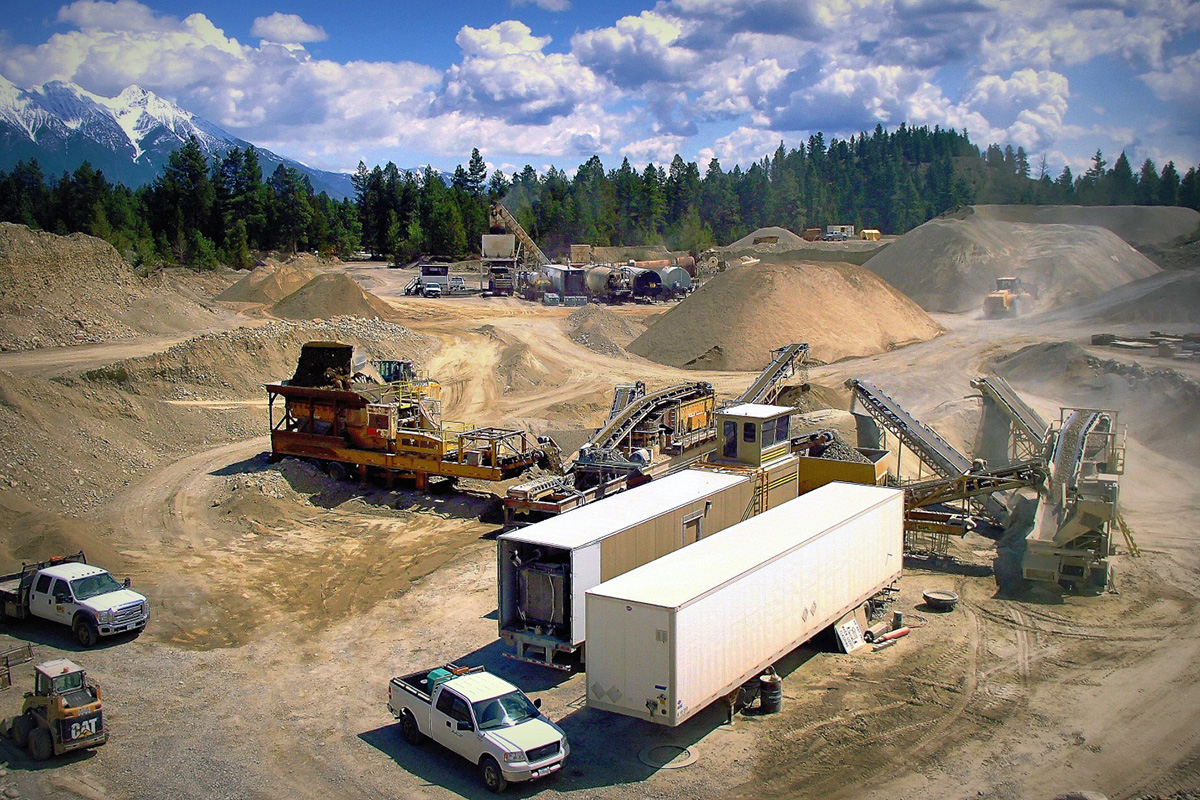 semi trailers and trucks working onsite with dirt roads