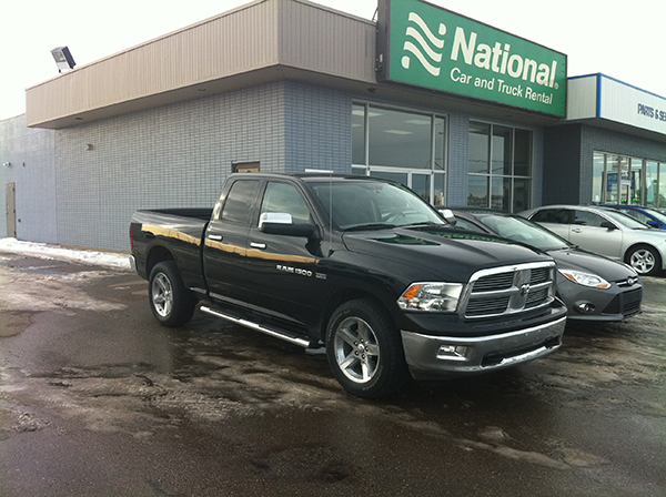 Truck parked outside building advertising National Car and Truck Rental