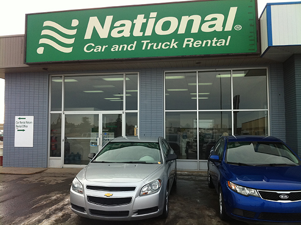 Car parked outside building advertising National Car and Truck Rental
