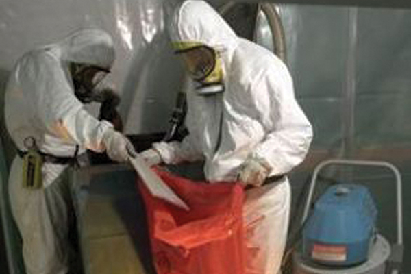 Two men in white gear putting drywall pieces in a red bag
