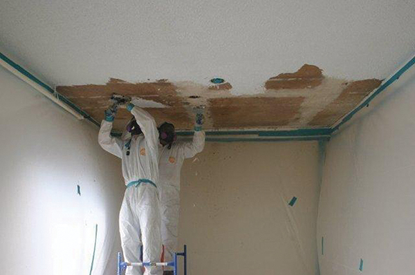 Two men in white gear scraping a ceiling