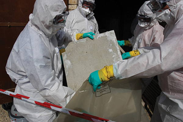 Team of men in white gear disposing of drywall pieces