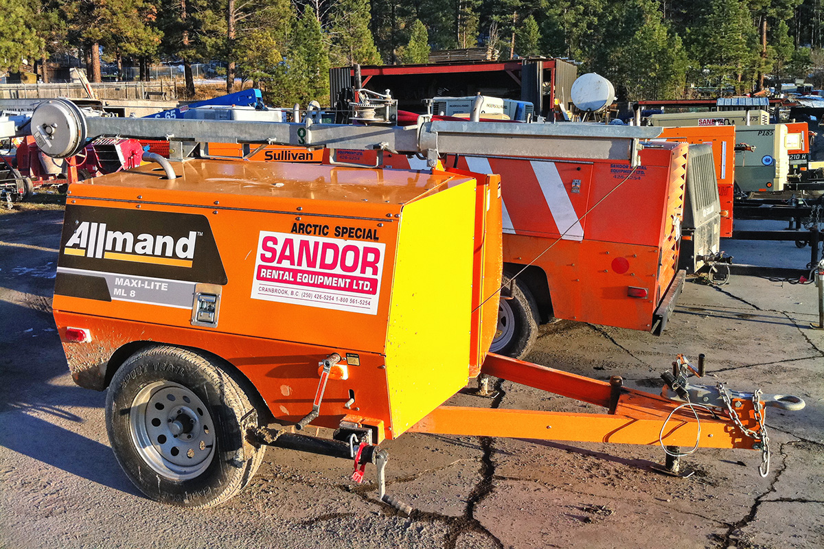 Orange and yellow Allmand trailer displaying company logo Sandor Rental Equipment 1981 limited