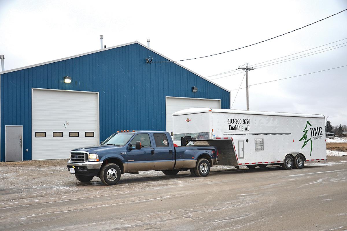 truck hauling a trailer advertising D M G Urethane Foam Services