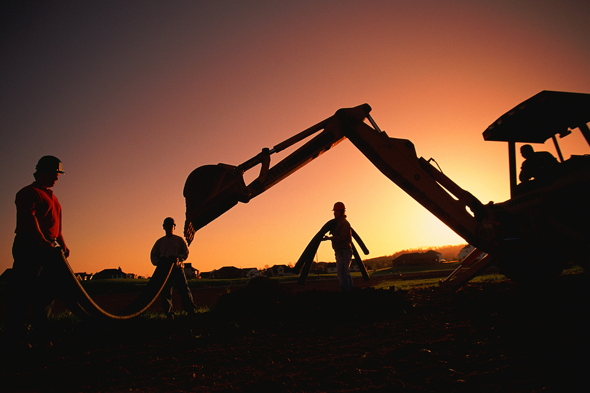 Silhouette picture of a backhoe with a sunset in the background