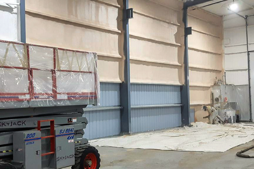 man spraying insulation on a wall inside a large industrial building