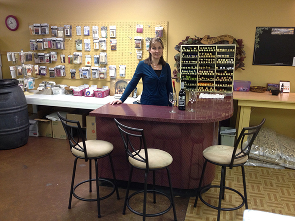 A lady standing at a circular table displaying wine