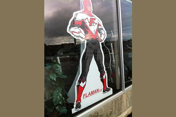 Cardboard man dressed in a heroic suit displaying Flaman