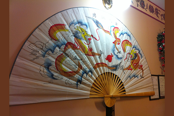 An oriental fan displayed on the wall