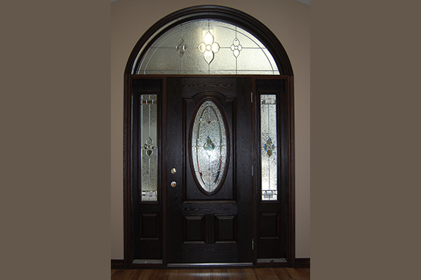 Dark coloured door with a semi-circle window above