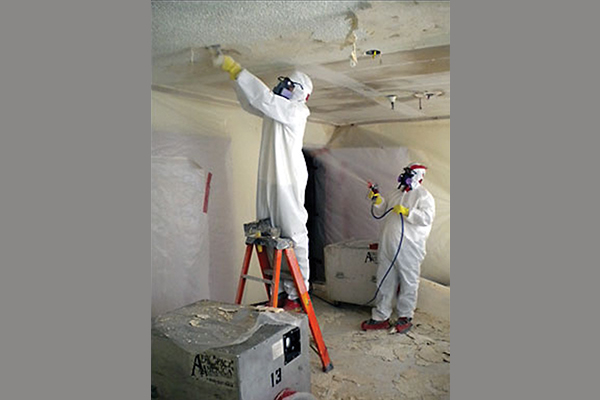 Man on a ladder scraping the ceiling while another man uses a sprayer