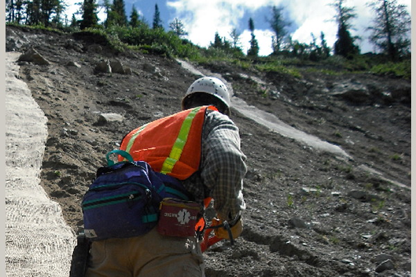 man dressed in safety gear measuring a dirt trail