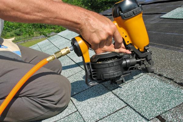 close up of a man nailing down shingles on a roof using a nailer