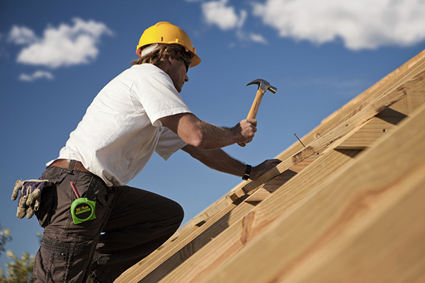Man on a roof hammering nails into a wooden roof in construction
