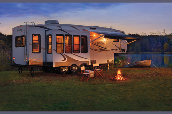 An RV parked outdoors during dusk with lights on inside and sliders opened