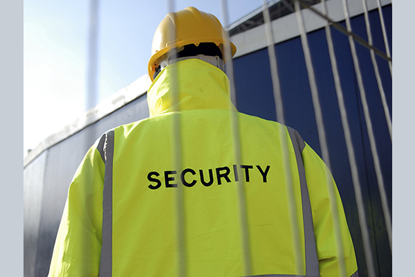 The back of a man standing guard wearing a security jacket
