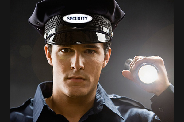 A man holding a flashlight up in uniform wearing a security hat