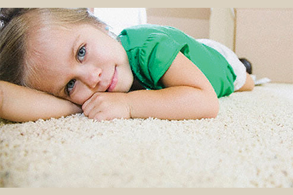 Little girl laying on carpet