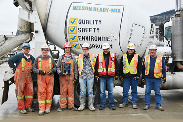 A team of men dressed in proper protective equipment standing in front of a gravel truck