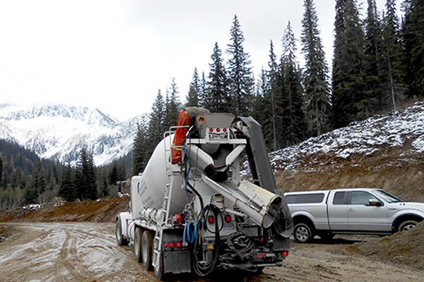 Gravel truck driving down a muddy dirt road