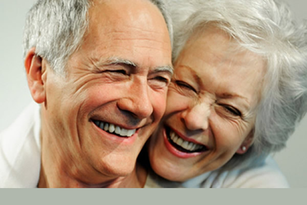 elderly couple smiling next to each other wearing dentures