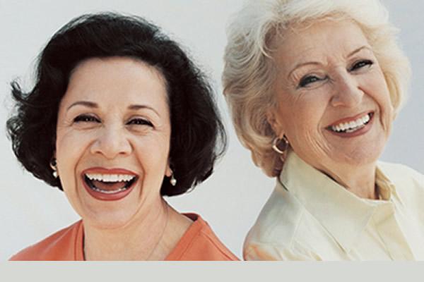 two elderly women smiling with comfort in wearing full dentures