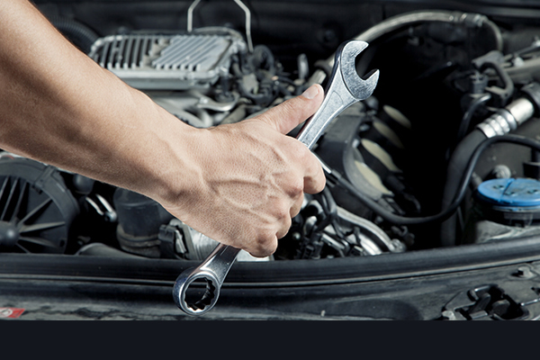 A hand holding a wrench over a vehicle engine