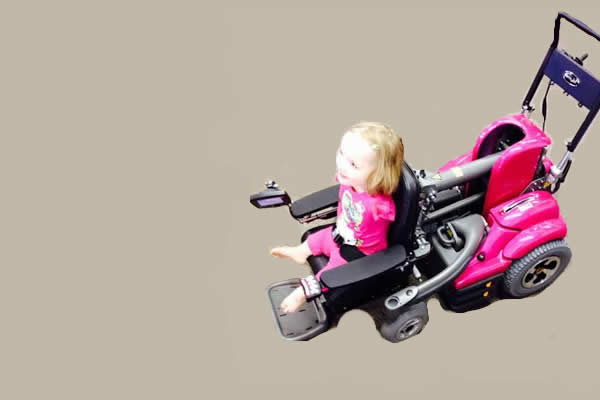 a little girl sitting in a black and pink custom wheelchair