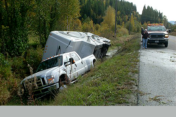 white truck and white camper rolled over in the ditch off the side of the highway