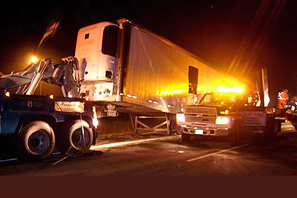 semi truck being towed away at the scene of an accident