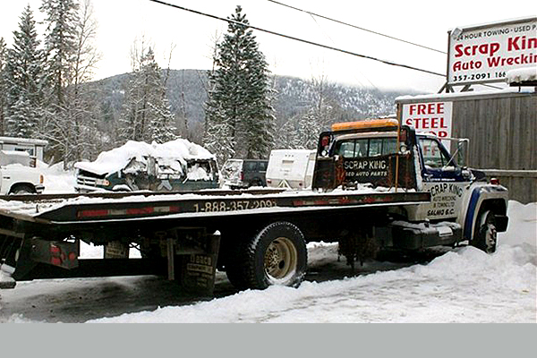 flat deck trailer and truck parked in the snow advertising Scrap King Auto Wrecking and Towing.