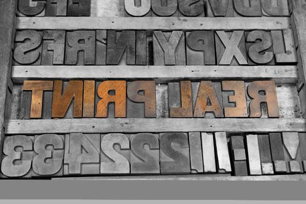 metal sign reading real print backwards