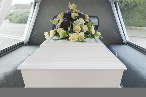 Casket inside a hearse with a flower arrangement on top