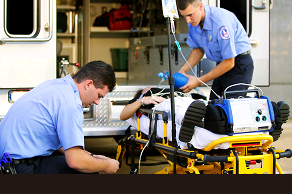 Two paramedics assisting a patient on a stretcher