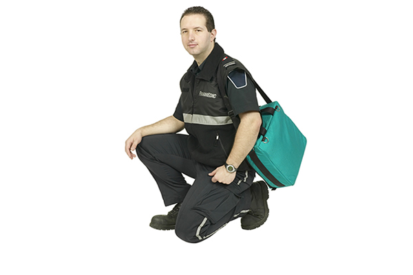 Male dressed in a paramedic uniform carrying a green bag