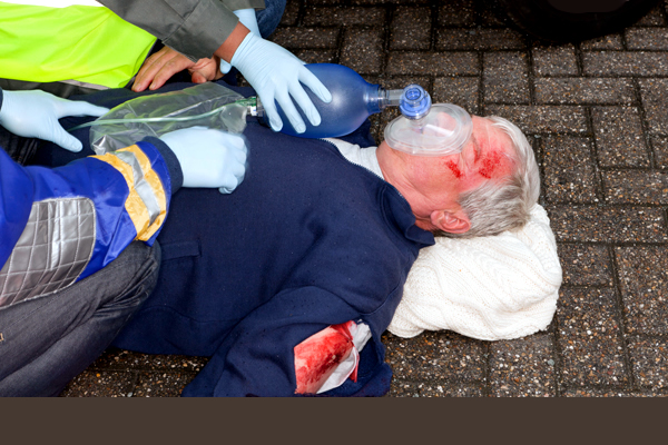 Two paramedics assisting a man laying down with an oxygen mask over his face