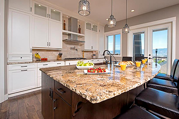 Open kitchen concept with granite countertop island and white cupboards