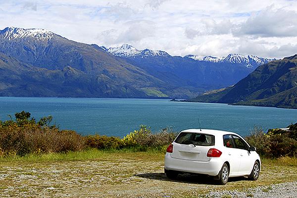 A white van parked alongside a lake