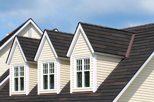 new tan siding and dark brown shingles on a home