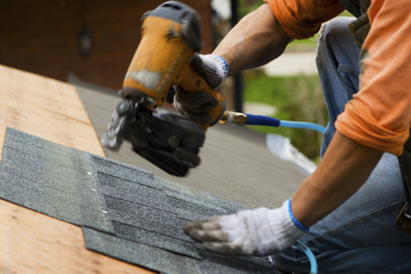 man operating a drill with shingles on a roof