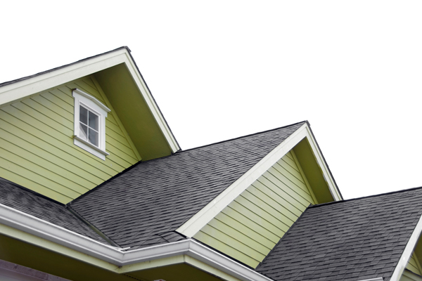 green siding on a home with dark brown shingles on a roof