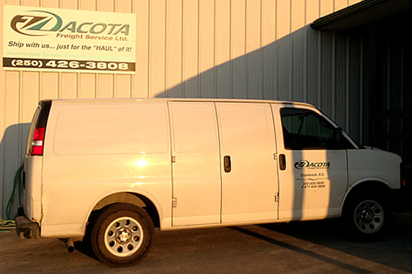 white company van advertising Dacota Freight Services parked next to exterior sign advertising Dacota Freight Services