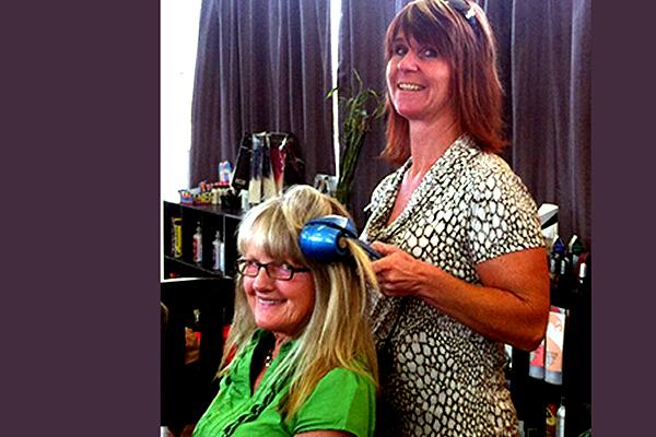 Seana Coolbaugh ironing Dodi Dube's hair