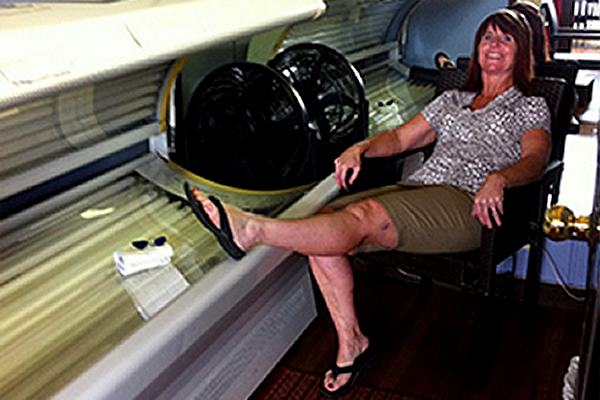 Seana Coolbaugh sitting next to a tanning bed